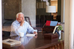 Memorias de la escritura del hombre mayor en el libro que se sienta en el escritorio Imagen de archivo