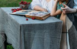 Memorie degli anziani Nonna di visita nonna con i suoi nipoti che si siedono in una sedia nel giardino e che guardano un ol fotografia stock