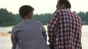 Memorie del padre e del figlio che spendono insieme tempo libero, godenti del tramonto del lago archivi video