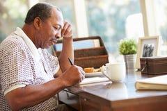 Memorie di scrittura dell'uomo senior in libro che si siede allo scrittorio Immagini Stock Libere da Diritti