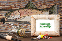 Memorie of the fishing trip. Reel, pole bobbers, jig on table with fish in background. White picture in birch frame can be changed to fit designers requirements royalty free stock images