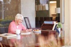 Memorie senior di scrittura della donna in libro allo scrittorio fotografia stock