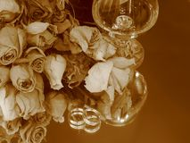 Memories. Closeup of a glass of brandy, dry roses bouquet, and a set of diamond rings over a mirror stock images