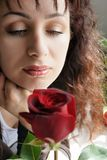 Memories. Beautiful Young woman looking at a red rose Stock Images