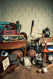 Memories from the attic. Assorted vintage items in the attic with retro wallpaper background Stock Photos