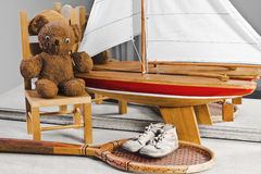 Memories From Childhood And Youth. This dresser has some items from childhood through youth. They include baby shoes, teddy bear on a little chair, sailboat, and Stock Images
