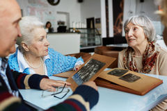 Memories. Friendly seniors talking while looking through photographs Stock Image