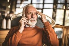 Memories. Senior man talking on cellphone. Memories. Senior man talking on cellphone at home stock photos