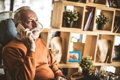 Memories. Senior man talking on cellphone. Memories. Senior man talking on cellphone at home royalty free stock images