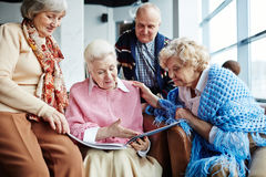 Memories. Senior women showing friends photos of her family Royalty Free Stock Images