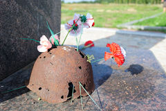 Memory. Rusty helmet remained from World War II and flowers brought in memory Royalty Free Stock Photo