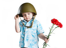 Memory. Boy with army helmet and carnations in his hand, isolated on white Royalty Free Stock Photo