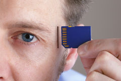 Memory and brain upgrade. Inserting SD memory card into slot in human head concept for memory upgrage, forgetfulness or computing Royalty Free Stock Photo