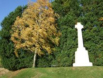 In Memory through Changing Seasons. The passing of seasons and colour changes with a memorial monument. A cross of stone against a backdrop of different coloured stock photos