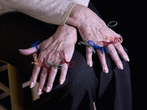 Memory. Close up of hands of an old woman, with strings attached in the fingers, remembering something Stock Images