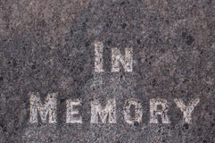 In memory inscribed on a gravestone. In memory white words written on a grey marble gravestone Royalty Free Stock Photo