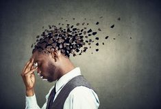Side profile of a sad man losing parts of head as symbol of decreased mind function. stock photo