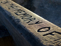In Memory of Bench. A memorial bench for a loved one. Carved in the wood are the words in memory of. Use this for remembrance or memorial works Stock Photo