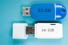 Memory sticks on blue background. Used, worn and slightly dusty USB memory sticks, backs up; one white and one blue, 16 GB and 32 GB, on blue background stock image