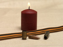 Memory of war. Burning candle, shell, bullet and St. George ribbon closeup Royalty Free Stock Photography