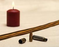 Memory of war. Burning candle, shell, bullet and St. George ribbon closeup Royalty Free Stock Photos