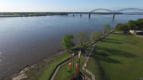 MEMPHIS, TENNESSEE - APRIL 11, 2016: Flying over the waving flags in Memphis. Mississippi river and cityscape in background stock video