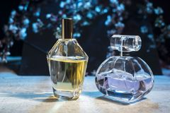 Men's en women's de parfums in een glasfles op een houten lijst tegen de achtergrond van de lente bloeien royalty-vrije stock foto