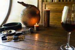Men's rings in bronze plate on a wooden table. Men's accessorizes, necktie, belt, watch Royalty Free Stock Photo