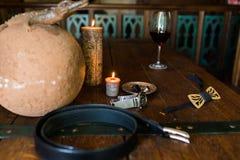 Men's suena en la placa de bronce en una tabla de madera y una vela ardiente Accesorios de Men's Corbata de madera Correa de  Imágenes de archivo libres de regalías