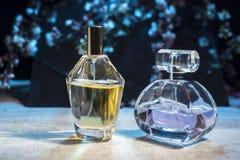 Men's y perfumes de los women's en una botella de cristal en una tabla de madera contra la perspectiva de las flores de la pr foto de archivo libre de regalías