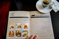 Menú árabe y una taza de café en un Dubai caf dubai Verano 2016 Foto de archivo libre de regalías