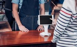 Menú de la bebida de la orden del servicio del uno mismo del cliente con la pantalla de la tableta en el caf imágenes de archivo libres de regalías