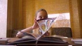 Menú de la lectura de la chica joven en el partido de cena del restaurante de Japanies - cierre divertido de la muchacha encima d metrajes