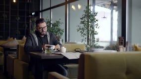 Menú de la lectura del hombre en la tabla en café almacen de video