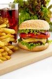 Menú del cheeseburger, patatas fritas, vidrio de cola en la placa de madera Foto de archivo
