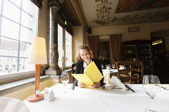 Menú sonriente de la lectura del cliente en la tabla del restaurante Foto de archivo libre de regalías