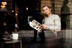 Menü des jungen Mannes Leseam Café mit Tasse Kaffee auf Tabelle, Reflexion im Fenster stockbild