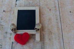 Menübrett im schwarzen und roten Herzen und ein menschlicher Schädel legen auf das w Stockfotografie