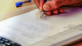 men& x27的特写镜头;在本文写着某事在笔帮助下的s手 免版税库存照片