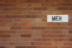 MEN. Public restroom sign on brick wall Royalty Free Stock Images