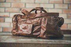 Men& x27; accesorios de s con los bolsos de cuero marrón oscuro en la tabla de madera o Imagen de archivo