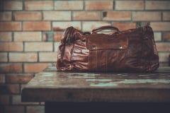 Men& x27; accesorios de s con los bolsos de cuero marrón oscuro en la tabla de madera o Fotos de archivo libres de regalías