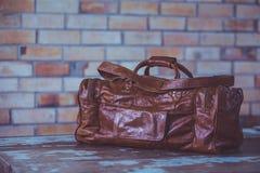 Men& x27; accesorios de s con los bolsos de cuero marrón oscuro en la tabla de madera o Fotografía de archivo