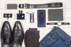 Men accessories. Black elegant accessories pieces  on white wooden table. Top view.  Stock Images
