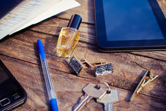 Men accessories cufflinks, tablet, perfume, pen, mobile phone, headphones, folder of documents and keys on the old wood backgroun Royalty Free Stock Images