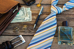 Men accessories: eau, cufflinks, dollars, strap, pen, mobile phone, document bag and key on the old wood background. Stock Photo