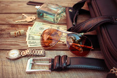 Men accessories. Sunglasses, bag, money, wrist watch, cufflinks, comb, strap, keys, perfume on the old wood background. Toned image Royalty Free Stock Images