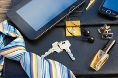 Men accessories: tie, cufflinks, tablet, perfume and keys on the old wood background. Stock Photos