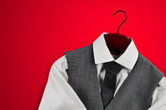 Men´s grey waistcoat, tie and white shirt on a clothes hanger on red background. Royalty Free Stock Images