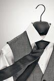 Men´s waistcoat, tie and white shirt on a clothes hanger in monochrome. Royalty Free Stock Images
